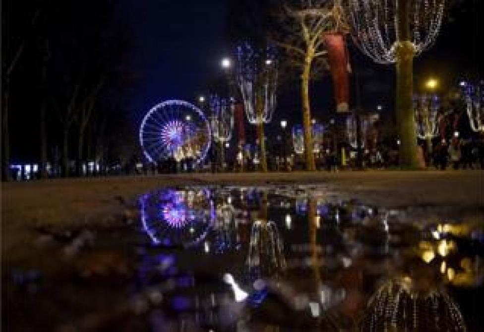 Luces y su reflejo en el agua adornan la Plaza de la Concordia en París.