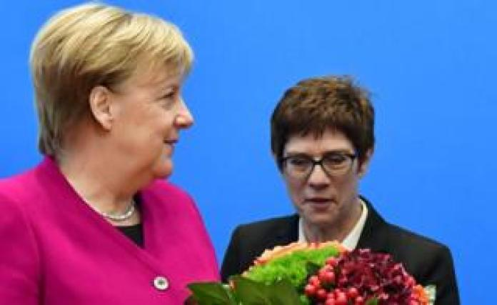 German Chancellor and leader of the Christian Democratic Union (CDU) Angela Merkel (L) receives flowers next to the Secretary General of the CDU, Annegret Kramp-Karrenbauer, before a meeting with the leadership of the CDU at the headquarters of the party, 29 October 2018 in Berlin