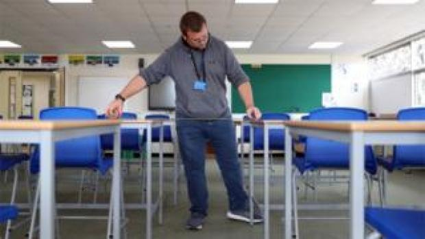 A school caretaker ensures desks are properly spaced