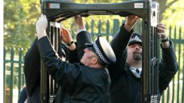 Police officers erect a metal detector arch at a school in Leyton, in east London, in 2009