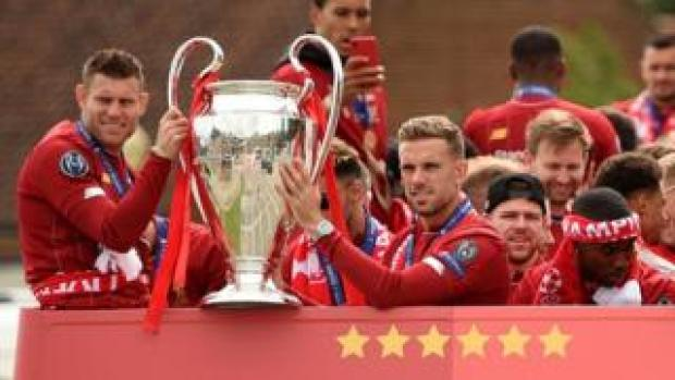 Liverpool midfielders James Milner (L) and Jordan Henderson hold the trophy on the bus