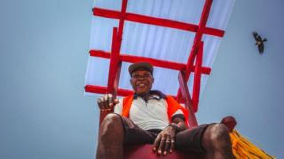 Lifeguard Stephen Boboly on chair with bird in view at Landmark Beach, Lagos, Nigeria