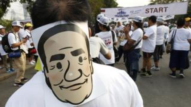 Supporters cheer and hold masks of Thai Prime Minister Prayut Chan-o-cha during pro-government protest