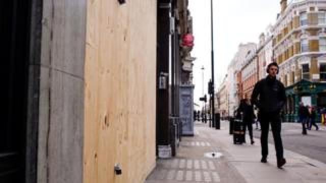 A man walks past a boarded-up shop on Mortimer Street in London, England, 2019.