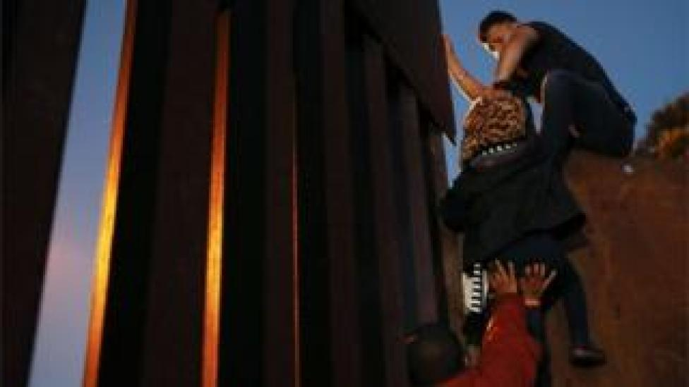 Members of the migrant caravan climb over the US-Mexico border fence on 3 December, 2018