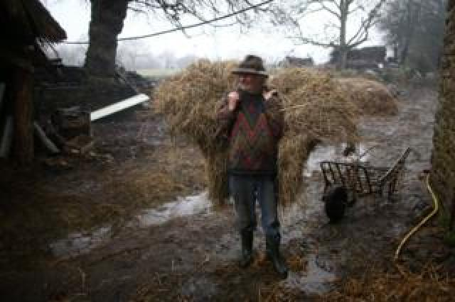 Farmer Jean-Bernard Huon stands on his farm with a bail of hay on his back.