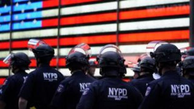 "In this file photo taken on June 01, 2020 NYPD police officers watch demonstrators in Times Square on June 1, 2020, during a ""Black Lives Matter"" protest"