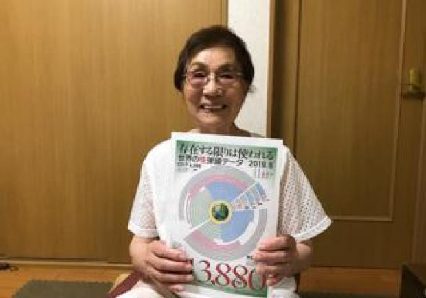 An elderly lady holds up a diagram to the camera