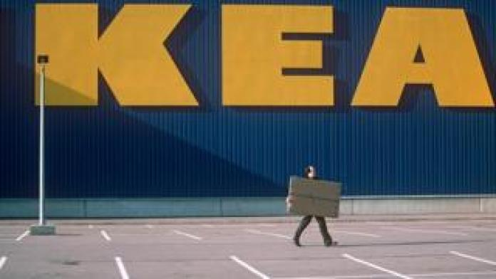 Man walking with a box in front of ikea sign
