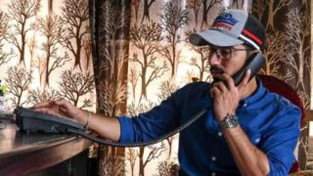 A Kashmiri Muslim talks on a landline phone in Srinagar on 17 August 2019