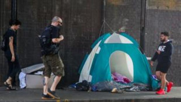 People walk past homeless person's tent in London in September