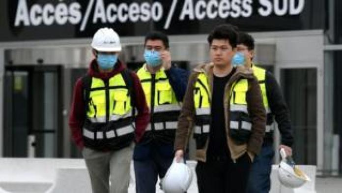 Workers leave the Mobile World Congress venue in Barcelona.