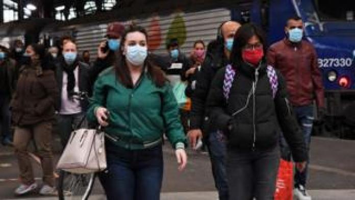Commuters wearing face masks cross Saint-Lazare station in Paris, May 11, 2020