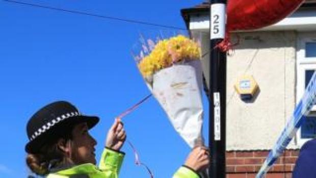 Police officer ties balloons to a lamppost