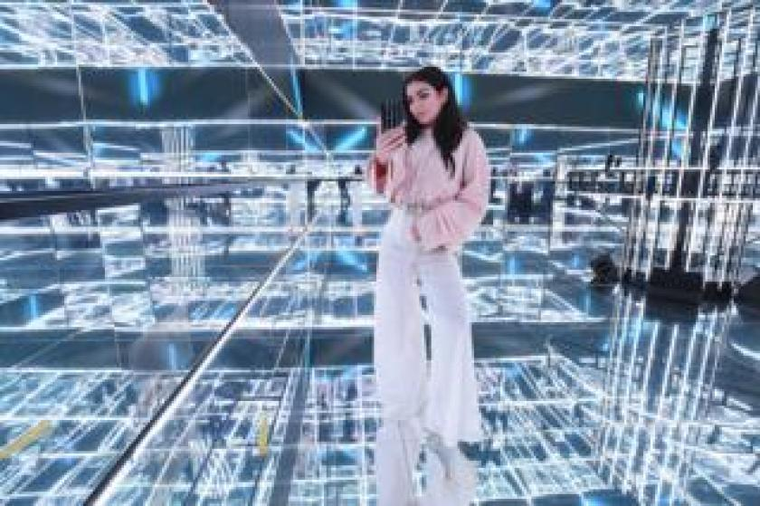 Charli XCX takes a photograph in a mirrored cube