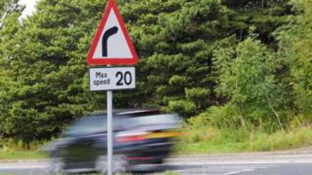 Car speeding past 20mph sign