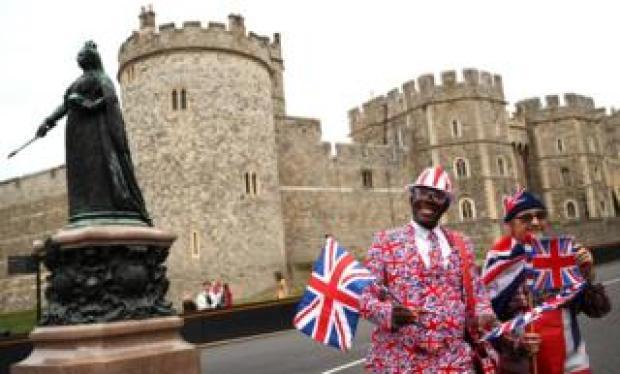 Royal fans Joseph Afrane and Sky London wave union jacks outside Windsor Castle on Thursday 11 October