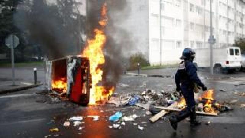 """A French riot policeman walks past a burning car as youth and high school students protest against the French government""""s reform plan, in Nantes, France, December 6, 2018"""