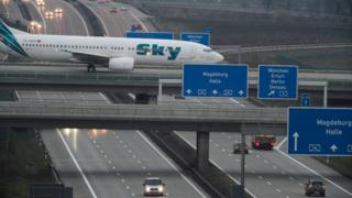 An aircraft crossing a busy motorway at Leipzig-Halle airport