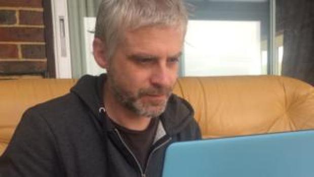 Iain Taylor, who writes fake reviews, sits at his laptop