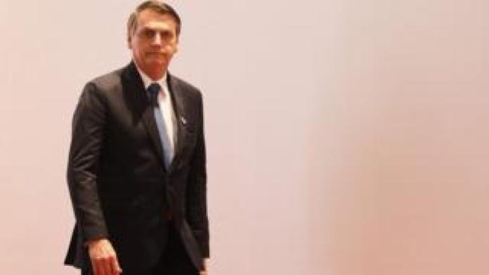 Bolsonaro aparece de terno e em pé na frente de fundo branco