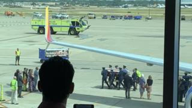 Col Knight is carried off the plane in Dallas