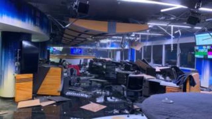 Newsroom with ceiling tiles fallen and broken computers