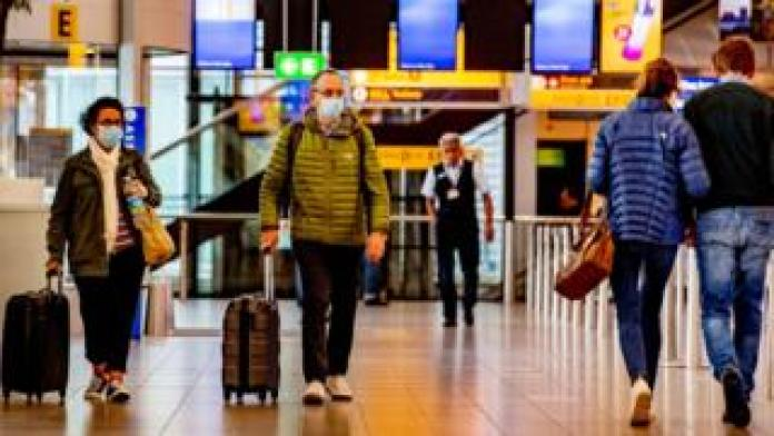 Travelers wearing facial masks as a precaution, on the KLM side at Schiphol Airport during the covid-19 pandemic.