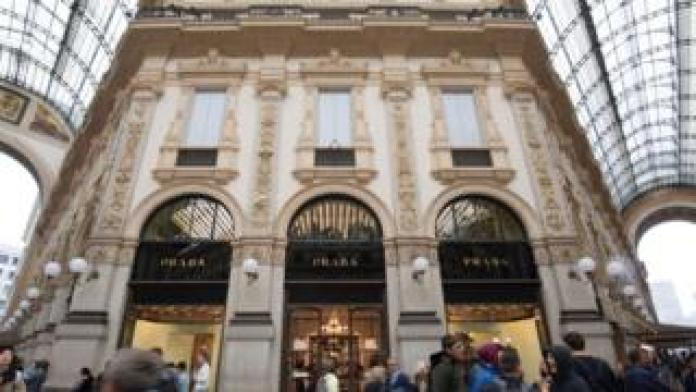 ourists and Milanese walk past luxury fashion shop Prada in the Vittorio Emanuele II luxury Gallery in the center of Milan