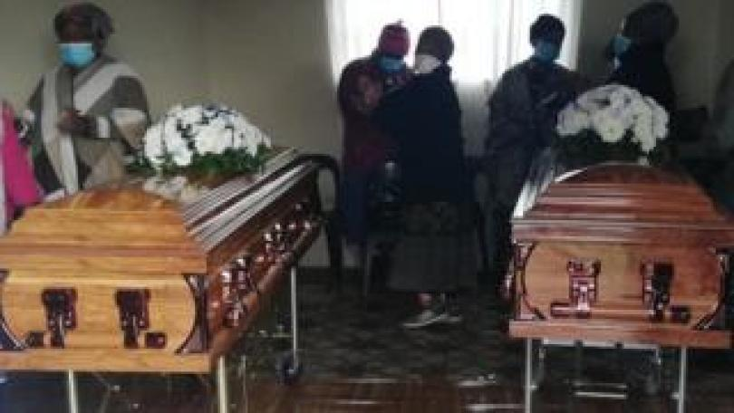 People standing by coffins