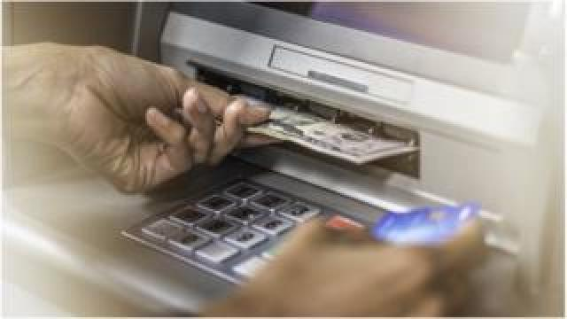 Stock image of person retrieving money from ATM