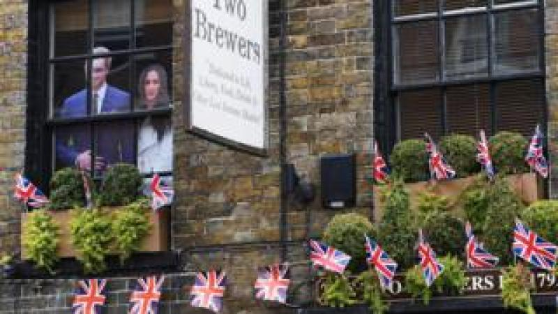 A cardboard cut out of Prince Harry and Meghan Markle stands in a pub window in Windsor