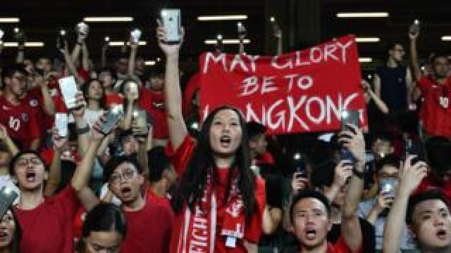 Football fans hold up their phones and shout during a protest at the end of the World Cup qualifying match between Hong Kong and Iran at Hong Kong Stadium on September 10, 2019