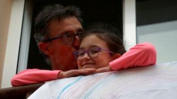 رجل يقبل ابنته بعد التصفيق دعماً العاملين في المجال الصحي