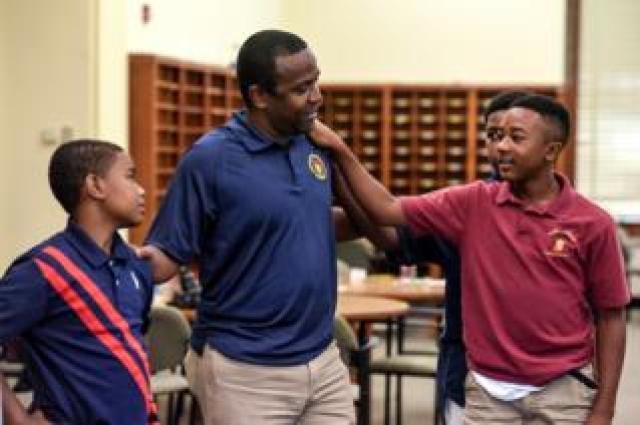Edwin Avent participates with students in a learning exercise at a summer session of a charter school called Baltimore Collegiate School for Boys