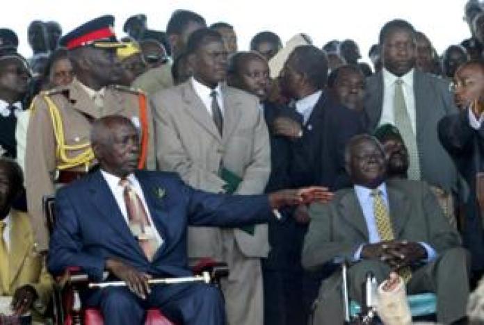 Daniel arap Moi sits next to President-elect Mwai Kibaki during the swearing-in ceremony in December 2002