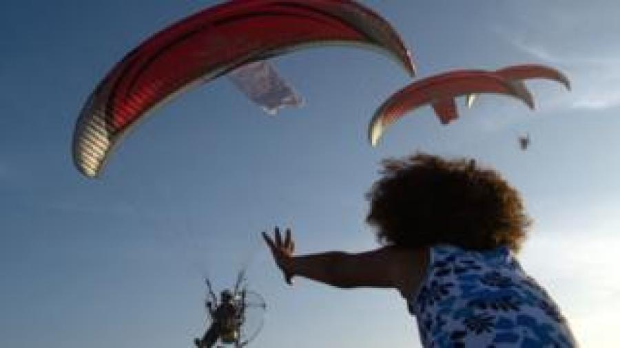 A girl reaches up towards military paragliders in Casablanca, Morocco - Saturday 30 September 2017
