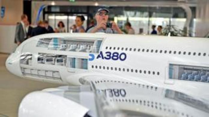 A visitor takes a photo of an Airbus aircraft model at company headquarters outside Toulouse