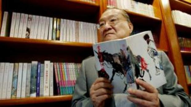 "Louis Cha holds his book ""Book and Sword, Gratitude and Revenge"" at his office in Hong Kong, 2002"