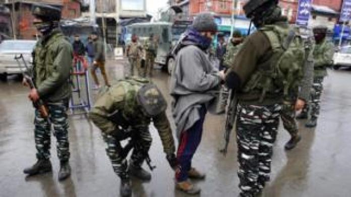 Central Reserve Police Force (CRPF) Indian paramilitary staff eats a Kashmiri man during a search operation in Lal Chowk, Srinagar, the summer capital of Kashmir, India, January 19, 2019.