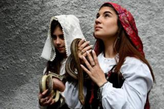 Faithfuls in traditional clothing hold snakes to place them on the statue of Saint Domenico during an annual procession in the streets of Cocullo