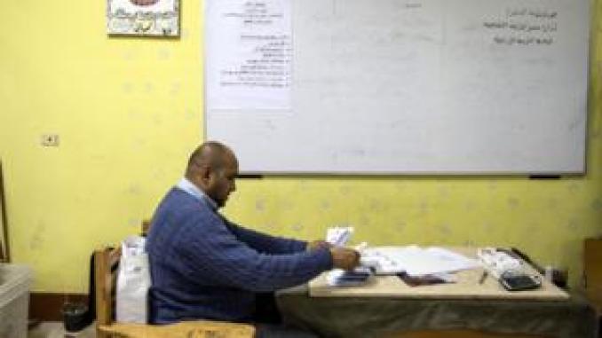 Man counting ballots at a desk