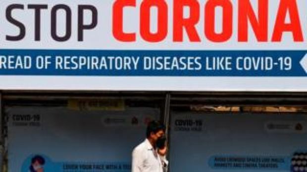 """An Indian man wearing a face mask walks past a giant sign reading """"stop Coronavirus"""""""