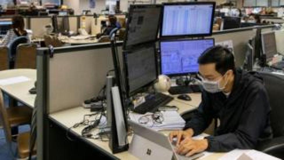A stock broker follows the Hang Seng Index in Hong Kong.