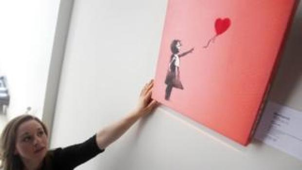 A Bonhams' employee adjusting a version of Banksy's Balloon Girl