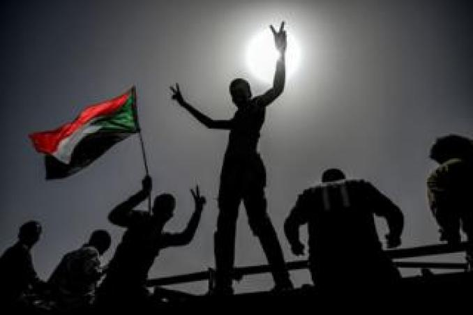 Sudanese protestors wave flags and flash victory signs as they continue to protest outside the army complex in the capital Khartoum on 17 April 2019.