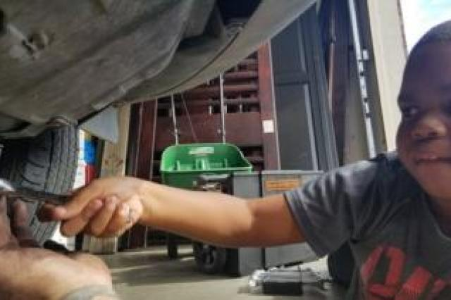 Tysen reaches out underneath his mum's car, with a helping hand from Adam