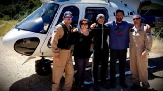 Krystal Ramirez (L), Hunter Whitson (C) and Curtis Whitson (R), pictured with rescue crew after their ordeal