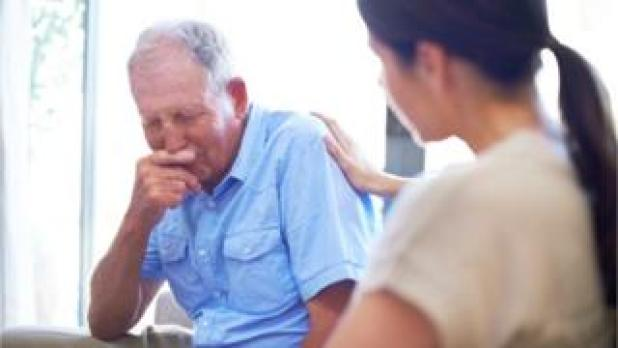 A young doctor talking to an older patient about his terminal illness