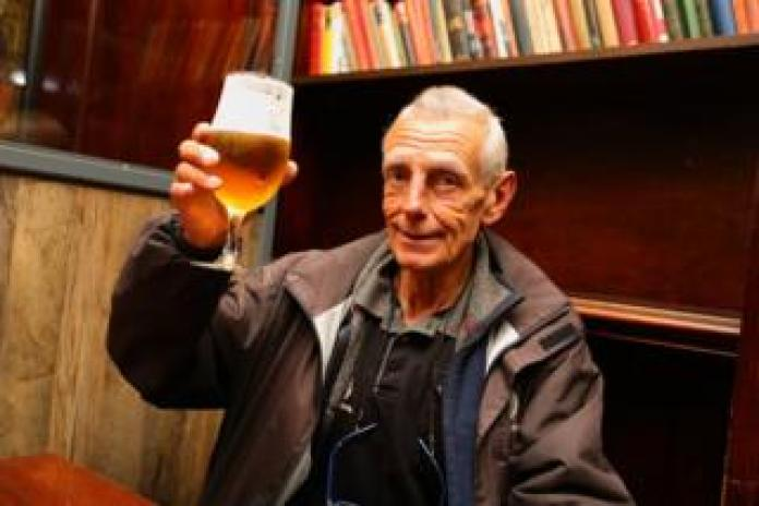 A man holds his pint of beer to the camera